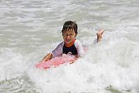 A small boy rides a wave using a body board at Kailua Beach, Oahu, Hawaii.