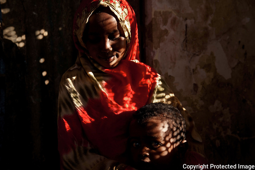 Juheriya, 12 years old, and Farah, 5 years old, in the  stairwell of  State House IDP camp. Hargeysa, Somaliland.
