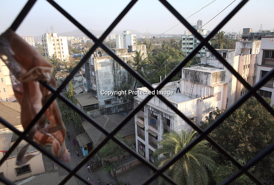 "The view from the hostel at the Rescue Foundation, a non-governmental organization founded to rescue young girls from brothels in and around Mumbai, India. The Rescue Foundation houses over 50 rescued girls at a time and some of them are Devadasis from the nearby ""Devadasi belt"" in Northern Karnataka. Most are under the age of 18 . For their own protection, the girls are not allowed to leave the Rescue Foundation building nor are they allowed to look out of the windows."