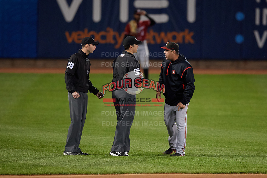 Altoona Curve manager Michael Ryan (12) argues a call with umpires Sean Shafer-Markle (left) and Mike Savakinas (center) during an Eastern League game against the Erie SeaWolves on June 3, 2019 at UPMC Park in Erie, Pennsylvania.  Altoona defeated Erie 9-8.  (Mike Janes/Four Seam Images)