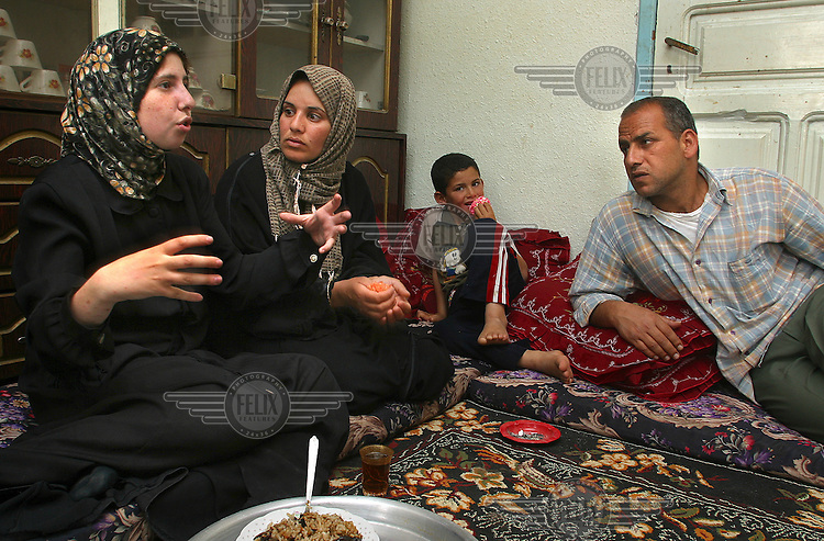 Laura (left)tells her Palestinian friends Nahed and Faud the news of the ISM office in Beit Sauhur (outside Betlehem) being raided by Israeli soldiers.