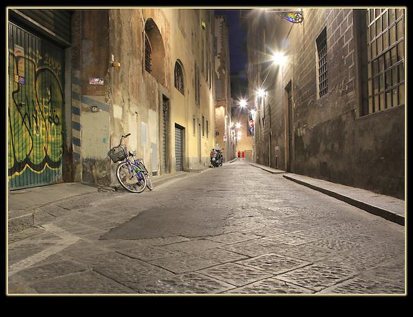 Couple walking on cobblestone street, Florence, Italy.