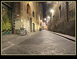 Couple walking on cobblestone street, Florence, Italy.