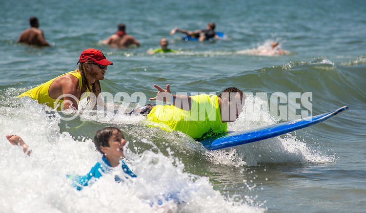 Lifeguard John Livingstone, 24 of Medford, New Jersey helps guide Anthony Tarquinio, 27, of Beuna, New Jersey on his paddle board during the 11th annual 21 Down Beach Day Monday, July 15, 2019 at Schellenger Street beach in Wildwood, New Jersey. Every summer, the Wildwood Beach Patrol opens Lincoln Ave Beach for kids with down syndrome and their families for 21 Down Beach Day. Often, kids with down syndrome aren't comfortable in the ocean. Their parents can't just relax and watch them frolic. But on July 15th, the kids swim with seasoned Wildwood lifeguards on soft-top paddle boards. (Photo by William Thomas Cain / CAIN IMAGES)