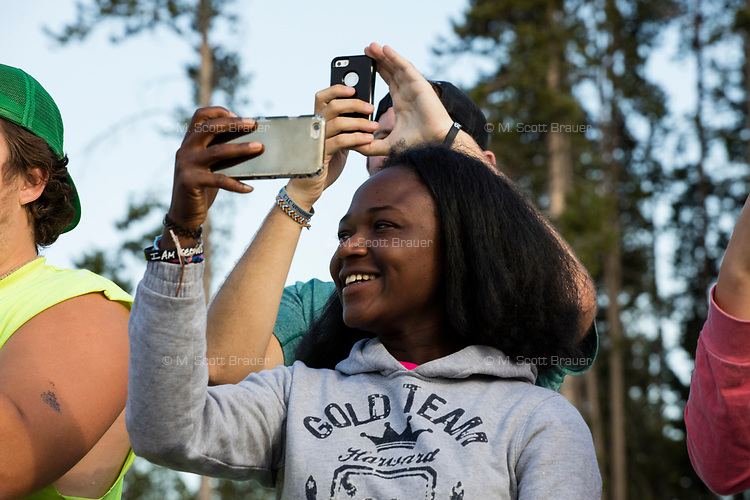 "Emmanuella Amanfo, of Italy, (center) smiles while watching Old Faithful erupt in Yellowstone National Park, Wyoming, USA. This was Amanfo's first visit to the US and Yellowstone. Asked about her impression of the park, she said, ""I've never seen anything like this."" In the days surrounding when this image was taken, the geyser averaged an eruption about every 90 minutes, though occasionally there were hours between eruptions."