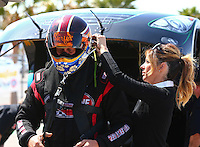 Mar 28, 2014; Las Vegas, NV, USA; NHRA funny car driver Jeff Diehl (left) is helped with his safety gear by wife Leeza Diehl during qualifying for the Summitracing.com Nationals at The Strip at Las Vegas Motor Speedway. Mandatory Credit: Mark J. Rebilas-