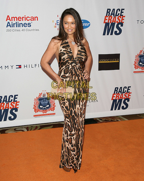 TIA CARRERE.The 18th Annual Race To Erase MS Gala held at The Hyatt Regency Century Plaza Hotel in Century City, California, USA. .April 29th, 2011.full length brown beige halterneck maxi leopard print dress clutch bag hand on hip.CAP/RKE/DVS.©DVS/RockinExposures/Capital Pictures.