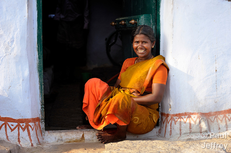 A woman sits in a doorway alongside a street in Sathangudi, a village in the southern Indian state of Tamil Nadu.