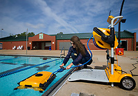 NWA Democrat-Gazette/JASON IVESTER<br /> Katie Morrison, recreation specialist for City of Bentonville, starts an automatic vacuum Friday, May 26, 2017, at the Melvin Ford Aquatic Center in Bentonville. The pool opens for the season today (SATURDAY).