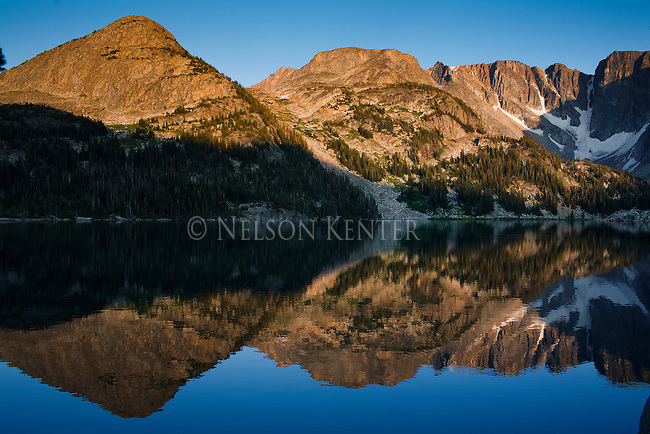 "Peaks of the Beartooth Mountains are reflected in the glass smooth surface of Dewey Lake high in the Beartooth Wilderness along the East Rosebud Trail. Also known as ""The Beaten Path"""