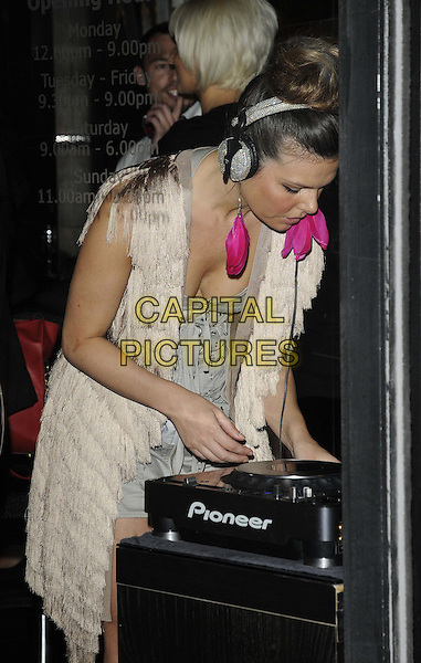 Jakki Degg.The Anesis Spa relaunch party, Anesis, The Pavement, London, England..August 31st, 2012.half length dj spinning records hairband silver cream fringed tassels dress  pink feather earrings cleavage bending leaning profile grey gray dress headphones .CAP/CAN.©Can Nguyen/Capital Pictures.