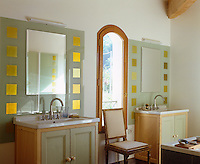 The bathroom has a pair of matching basins and mirrors set in glass panels