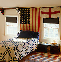 Amercian and English flags decorate this boy's bedroom with a blue and white patchwork quilt on the bed