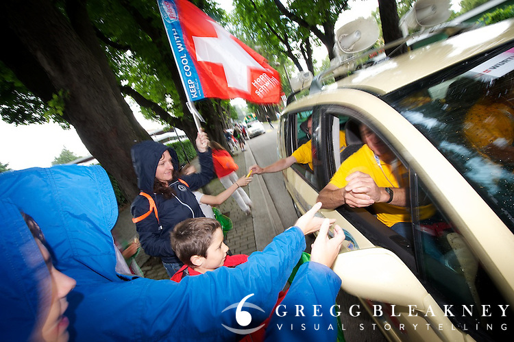 At the Tour de Suisse, fans get packaged cheese hand-out from promo cars before the prologue start.