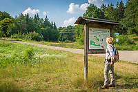 Deutschland, Bayern, Mittelfranken, Naturpark Altmuehltal, bei Solnhofen: Wanderer im Naturschutzgebiet Juratrockenhang mit der Felsgruppe Zwoelf Apostel vor einer Informationstafel | Germany, Bavaria, Middle Franconia, Nature Park Altmuehl Valley, near Solnhofen: hiker at rock formation 12 Apostles (nature reserve) reading information board