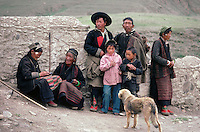 Life is incredibly harsh for the scattering of peasants who live on the high Tibetan plateau. Here, a group (and their dog) pause from the daily struggle for a moment but the snows of winter are not far away.