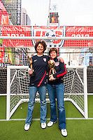Former women's national team players Michelle Akers and April Heinrichs pose with the World Cup trophies during the centennial celebration of U. S. Soccer at Times Square in New York, NY, on April 04, 2013.