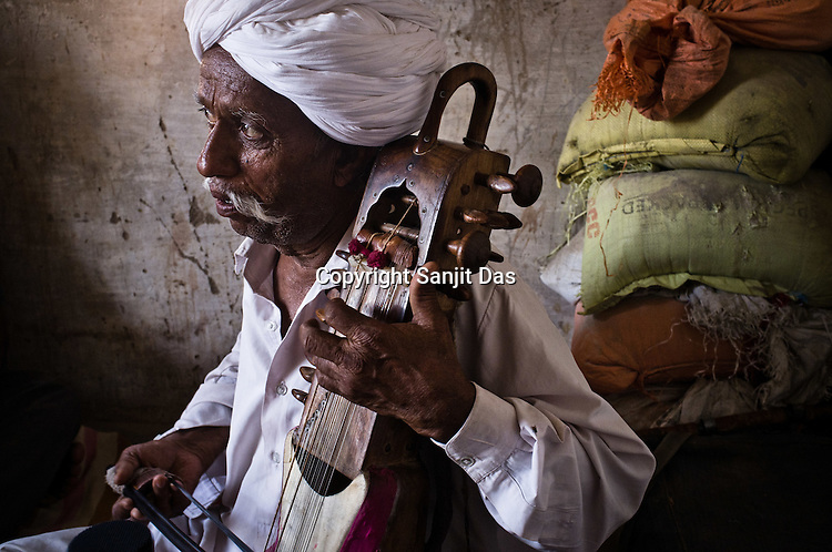 66-year-old Manganiyar artist, Lakha Khan plays the Sarangi in his house in Raneri village of Jodhpur district in Rajasthan, India. Photo: Sanjit Das/Panos