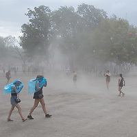 Revellers preparing for rain fight a sand storm caused by high wind before storm arrives to Sziget Festival held in Budapest, Hungary on Aug. 14, 2018. ATTILA VOLGYI