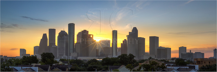 On a mild September morning, the Houston skyline awakens in this panorama image captured at the moment the sun peeked over downtown. This image is a stitch of several photographs and attempts to capture the cityscape at dawn. <br /> <br /> Prominent in this image is the tallest building in Texas, the JP Morgan Chase Tower, at 75 stories high. Houston is the largest city in Texas and 4th largest in the United States.<br /> <br /> This panorama is available both as a fine art print or for licensing as a digital file.