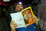 Andean Mountain Cat (Leopardus jacobita) biologist, Mauro Lucherini, reading National Geographic magazine, Loma Blanca, Abra Granada, Andes, northwestern Argentina