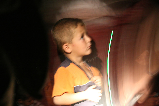 A young boy steps up to have a U.S. soldier wave a hand-held metal detector over him during a night raid on a suspected insurgent compound near the town of Sayafiyah, Iraq, south of Baghdad. Aug. 15, 2007. DREW BROWN/STARS AND STRIPES