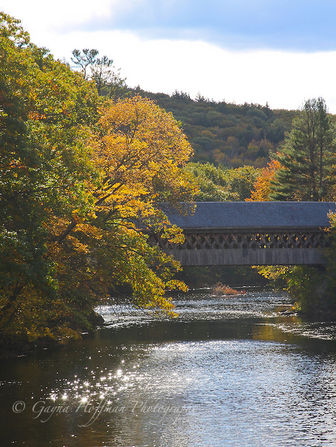 Covered bridge over a river. Fall, New Hampshire
