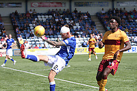 Scott Mercer clears as Devante Cole advances in the SPFL Betfred League Cup group match between Queen of the South and Motherwell at Palmerston Park, Dumfries on 13.7.19.