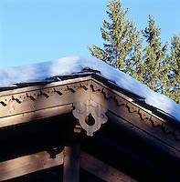 Wooden detailing on the exterior of the chalet, its roof laden with a thick covering of snow