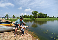 NWA Democrat-Gazette/CHARLIE KAIJO Hannah Cicioni of Rogers and Jude Azzain, 4, of Tulsa, Okla. (from left) skip rocks, Friday, July 5, 2019 at the Thaden field house dock across from Lake Bentonville Park in Bentonville. <br /> <br /> Lake Bentonville Park is undergoing a major renovation and will be closed July 8 through spring 2020