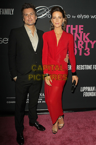 Len Wiseman, Kate Beckinsale<br /> The Pink Party 2013 held at the Santa Monica Airport, Santa Monica, California, USA.<br /> October 19th, 2013<br /> full length dress red black clutch bag  wrap black suit married husband wife <br /> CAP/ADM/KB<br /> &copy;Kevan Brooks/AdMedia/Capital Pictures