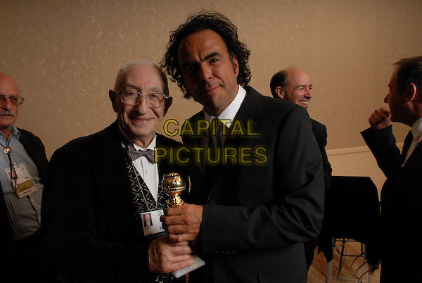 "YANI BEGAKIS (HFPA MEMBER) & ALEJANDRO GONZALEZ INARRITU .Winner Best Motion Picture-Drama for ""Babel"" .Pressroom - 64th Annual Golden Globe Awards, Beverly Hills HIlton, Beverly Hills, California, USA..January 15th 2007. .globes press room half length black suit jacket award trophy director profile.CAP/AW.Please use accompanying story.Supplied by Capital Pictures.© HFPA"" and ""64th Golden Globe Awards"""