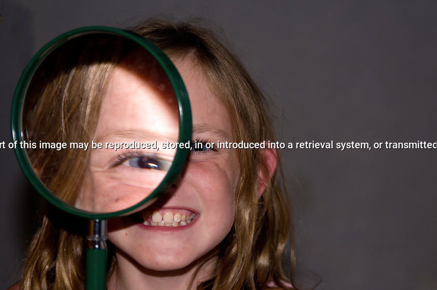 Young girl looking trhough a magnifying glass