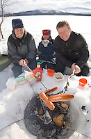 Sweden, SWE, Kiruna, 2006-Apr-16: Barbecue party in Lapland: a man and a woman sitting on the banks of the frozen Holmajarvi lake grilling sausages, while their four years old daughter between them is drinking juice. - NOTE: the focus is on the sausages, the people are blurry.