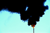 A petrochemical refinery flare and black smoke polluting the blue sky.