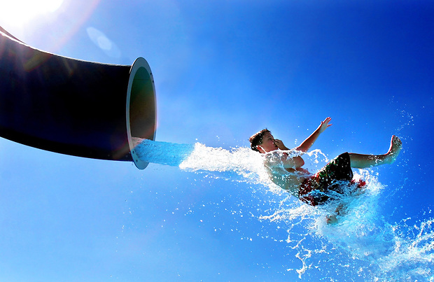 Clive Elementary School fourth grader Mark Fowler, 9, of Windsor Heights takes a watery flight from of a slide Tuesday, August 30 at the Clive Aquatic Center.   The entire school earned a three hour trip to the pool after the student body met summer readership goals.