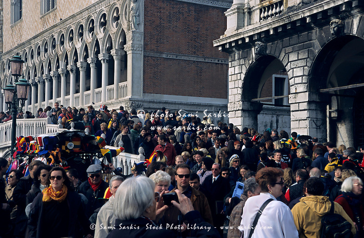 Crowds of tourists on a bridge during carnival by Doges Palace, Venice, Italy.