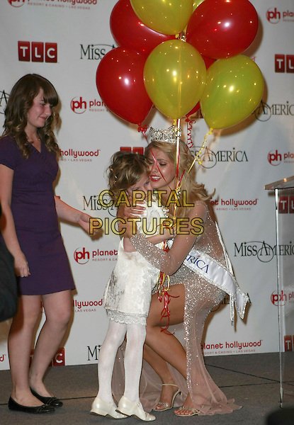 2008 MISS AMERICA KIRSTEN HAGLUND - MISS MICHIGAN (pictured with Children's Miracle Network).First Official Press Conference. 2008 Miss America Live! held at Planet Hollywood Hotel Casino, Las Vegas, Nevada, USA..January 26th, 2008.full length crown sparkly dress sash split slit balloons kids bending crouching hug embrace .CAP/ADM/MJT.©MJT/AdMedia/Capital Pictures. *** Local Caption *** .