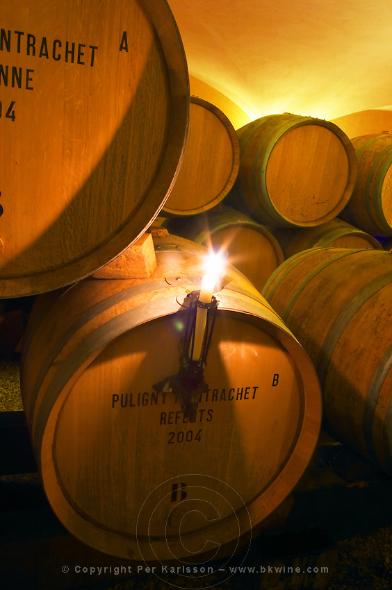 The old style vaulted barrel aging cellar with barriques pieces with maturing wine. A burning candle on a barrel used for controlling if a racked wine is clear or cloudy, Maison Louis Jadot, Beaune Côte Cote d Or Bourgogne Burgundy Burgundian France French Europe European