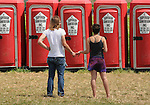 A couple waiting for a vacant portable toilet at the Falcon Ridge Folk Festival, held on Dodd's Farm in Hillsdale, NY on Sunday, August 2, 2015. Photo by Jim Peppler. Copyright Jim Peppler 2015.