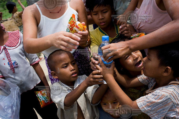 Children and women from the 7th ward, Hlaingthaya township in Rangoon (Yangon) struggle to get drinking water distributed by people from the city, having been displaced after Cyclone Nargis hit the Irrawaddy Delta on 02/05/2008.