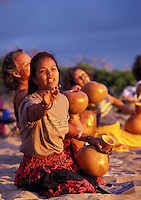 Hula dancers at Makapuu point dancing a noho hula with ipu ( gourd)  at sunrise on the beach