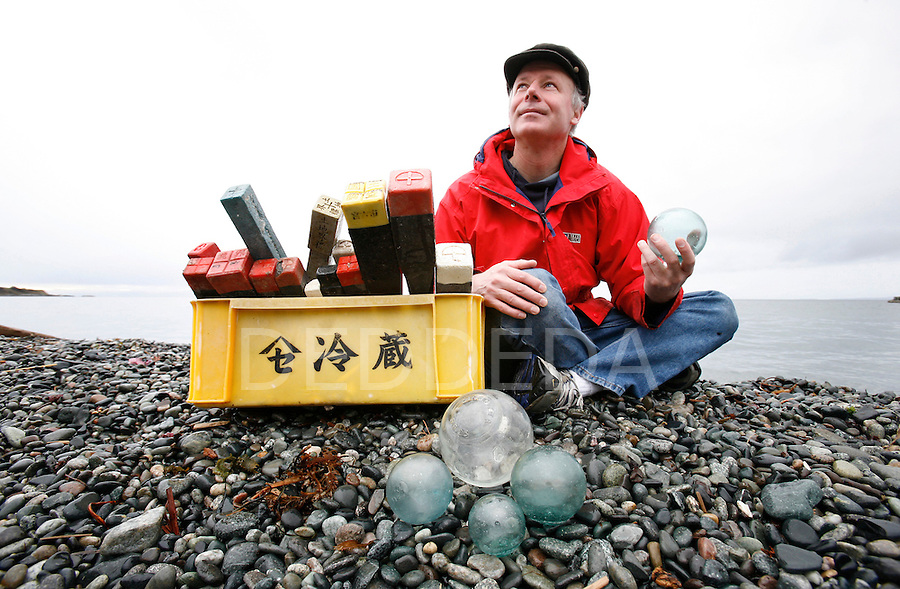 Brian Gisborne, a former commercial fisherman, displays some of his collection of flotsam, including plastic Japanese property markers, a yellow Chinese crate, and Japanese glass floats found off the westcoast of Vancouver Island, at a beach near his home in Victoria, British Columbia. Photo assignment for the Globe and Mail national newspaper in Canada.