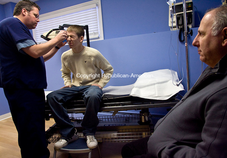 SOUTHBURY, CT - 25 DECEMBER 2008 -122508JT01-<br /> Rob Caleca, 18, winces as R. Robert Rohatsch, MD, left, takes a look to see if the five stitches on Caleca's eyebrow are ready to be taken out on Thursday, Christmas Day, at Urgent Care of Southbury. At right is Caleca's father, John Caleca. Rob Caleca had received the stitches five days ago at Urgent Care, when he received an injury during a wrestling match he was competing in for Pomperaug High School. Rob Caleca and his father had immediately come to Urgent Care, where Rob was stitched up within an hour, leaving him enough time to go back to the match and win.<br /> Josalee Thrift / Republican-American