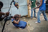 Film actress Adaobi Enekwa playing a woman attacked by vigilantes on the set of a Nollywood movie production.