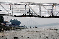 A man pushes his bike across a bridge on the banks of the Ganges River in Kolkata.<br />