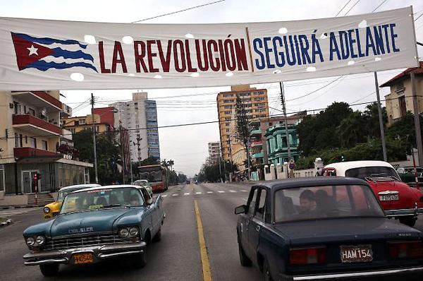 HAB01. LA HABANA (CUBA), 31/12/2013.- Varios autos circulan hoy, martes 31 de diciembre de 2013, por una céntrica avenida bajo un cartel alusivo a la revolución cubana en La Habana (Cuba). En medio de un ambiente tranquilo y sin gran resonancia, Cuba se prepara para celebrar mañana los 55 años de su revolución con un acto político en la ciudad de Santiago, al que se prevé que acuda el presidente, Raúl Castro. EFE/Alejandro Ernesto