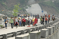 Refugees flee their mountain homes for the lowland city of Chengdu as landslides and aftershocks continue following the 12th May earthquake. .15 May 2008