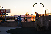 A moment in time at a neighborhood park: an airborne basketball, a father,  kids climbing, sun setting.