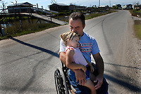 Juliette Brunet sits with her uncle, Chris Brunet in a wheelchair who is Juliette's guardian since the death of both of her parents. The live on the only road in the predominantly Native American community of Isle de Jean Charles, Louisiana. The island is particularly affected by coastal erosion. Residents are seeking higher ground and only 70 residents remain of the 300 residents at the peak of population.